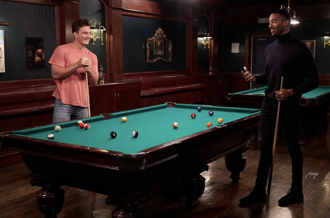 Matt James and Tyler C play pool on episode 6 of the bachelor. Matt and Tyler C are standing around a green felt pool table.
