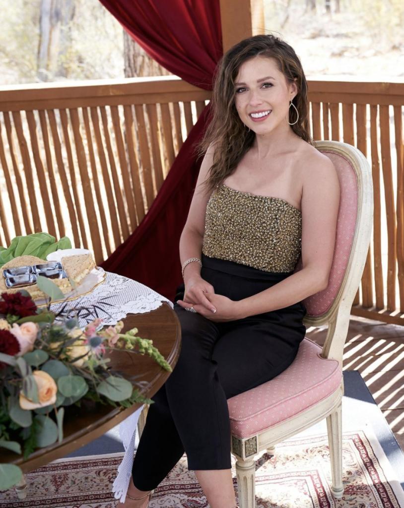 Katie Thurston sitting in a black jumpsuit